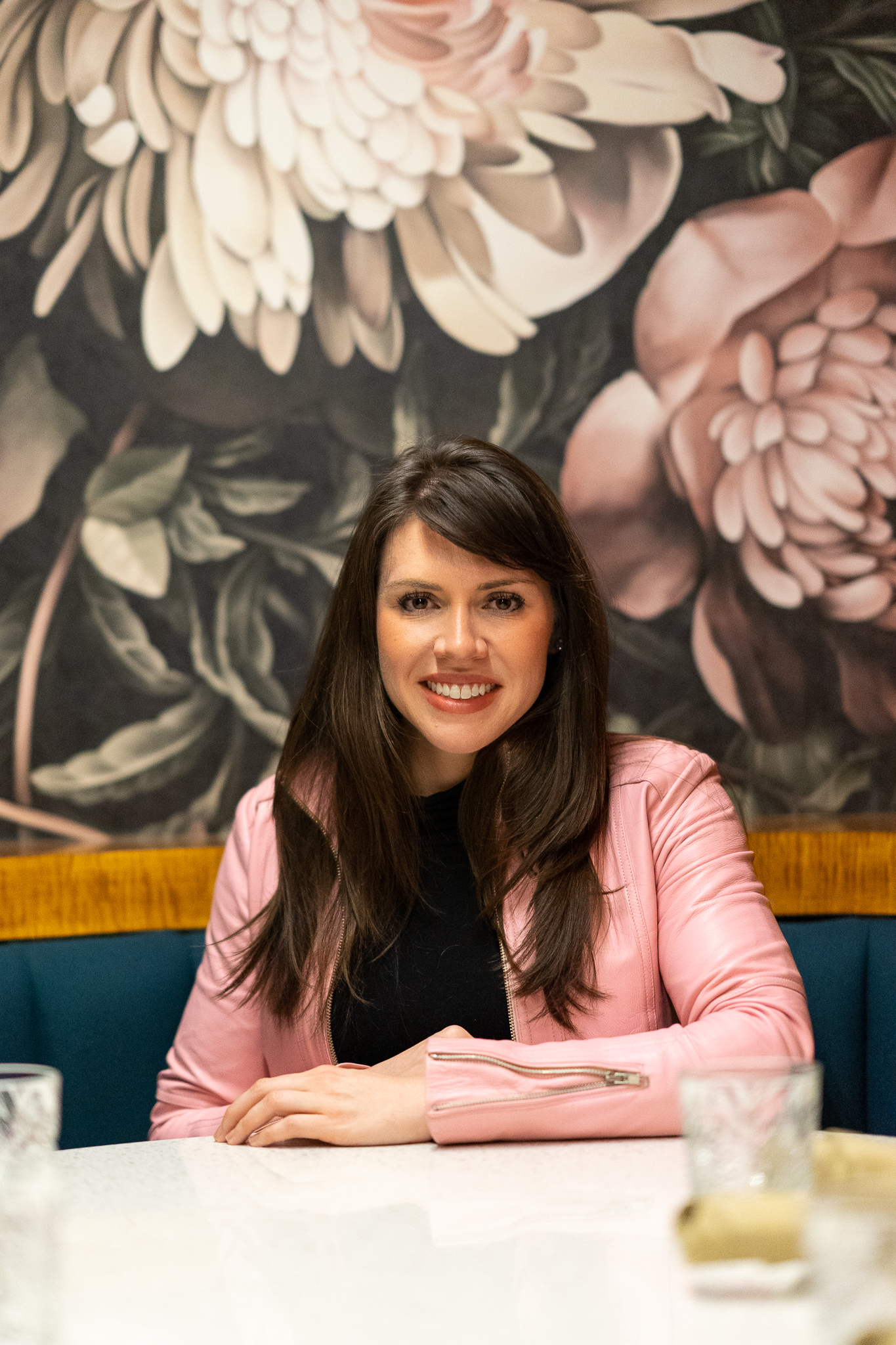 Photo of Julia Bonner. Julia is a communications expert and founder of Pierce Public Relations. Julia is sitting at a table at Mockingbird Restaurant, Nashville, TN, wearing a pink leather jacket and a beautiful, natural smile. Julia is surrounded by a floral wallpaper backdrop.